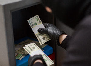 Burglar stealing cash from a safe