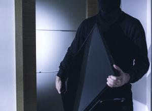 Burglar stealing a TV from a home