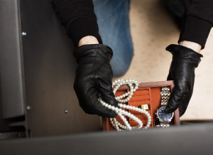 A burglar stealing a pearl necklace, a watch and other jewelry from a home