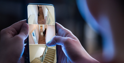 monitoring a home using a wireless camera system accessible through a mobile phone
